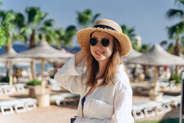 Mädchen mit strohhut am hotelpool mit sonnenschirmen und palmen herum