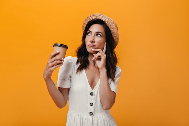Mädchen mit strohhut schaut nachdenklich auf und hält ein glas kaffee. nachdenkliche frau in weißen sommerkleidern mit kaffee in ihren händen posierend.