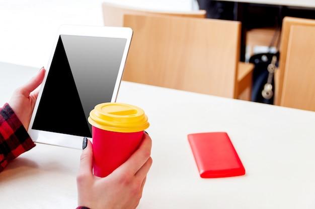 Mädchen mit tablette in der hand und tasse kaffee / tee, die im café im winter sitzen