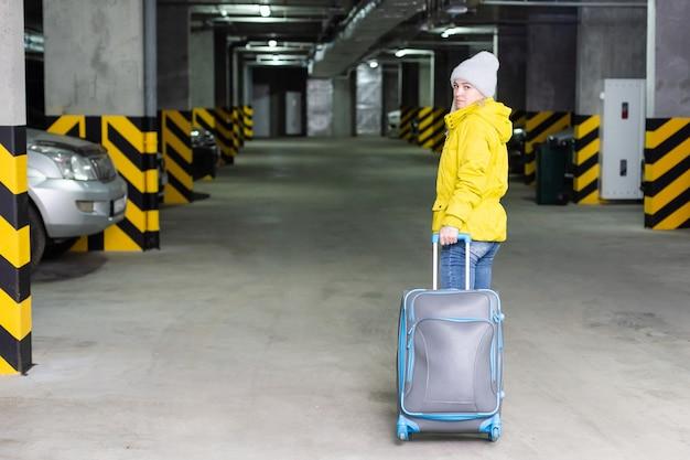 Mädchen mit tasche auf dem parkplatz am flughafen