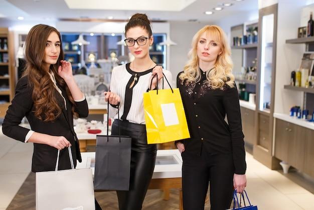 Mädchen mit taschen in einer boutique.
