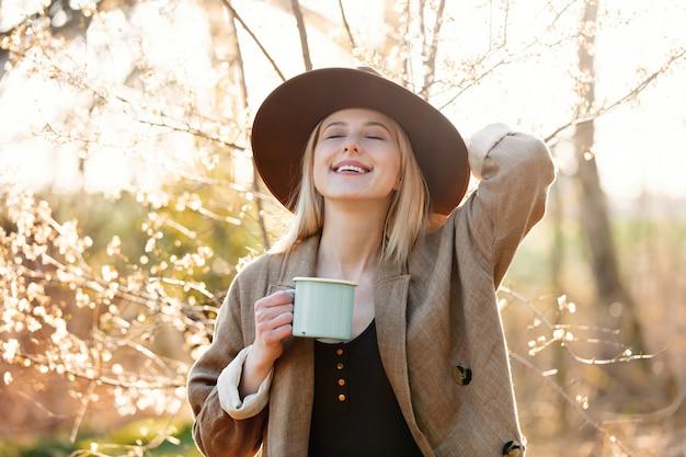 Mädchen mit tasse kaffee in einem kirschblütengarten bei sonnenuntergang