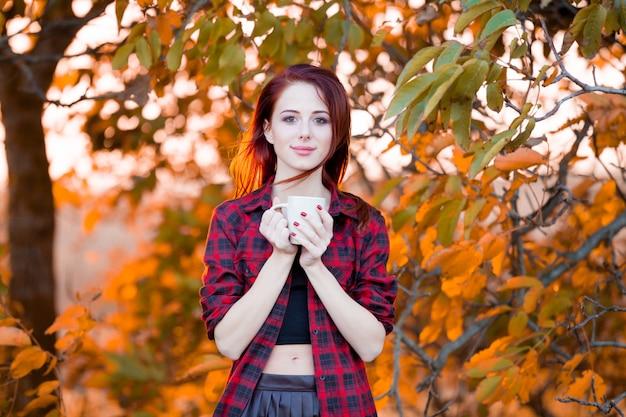 Mädchen mit tasse kaffee zur herbstzeit