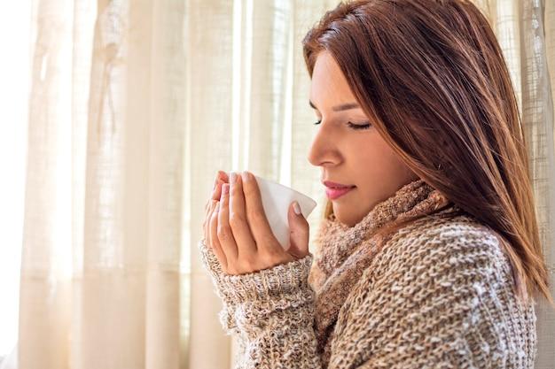 Mädchen mit tasse tee zu hause während des winters