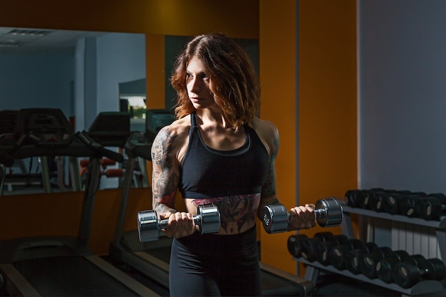 Mädchen mit tattoos auf fitness hebt hanteln