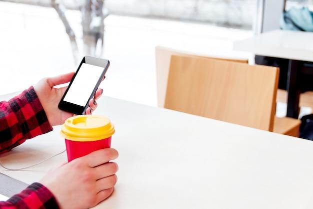 Mädchen mit telefon in der hand und tasse kaffee / tee im café im winter sitzen