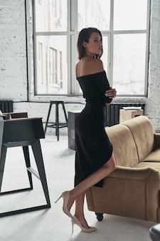 Mädchen mit tollem stil. die volle länge der attraktiven jungen frau in einem eleganten schwarzen kleid mit einem tiefen schlitz, der die arme verschränkt hält, während sie in der nähe des sofas steht