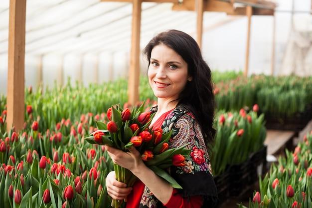 Mädchen mit tulpen in einem gewächshaus gewachsen.