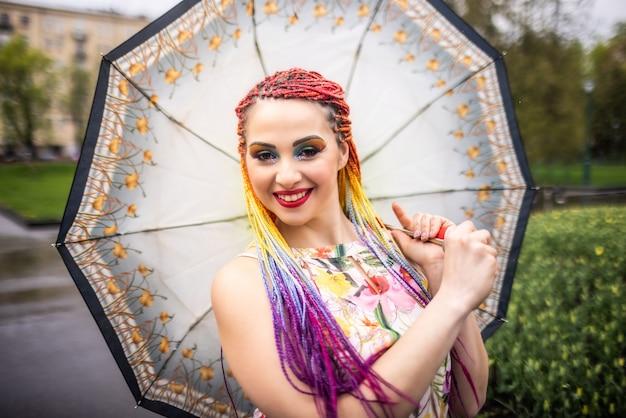 Mädchen mit ungewöhnlichem glitzer-make-up mit bunten faux-zöpfen in einem kleid mit blumendruck. mit regenschirm herumwirbeln