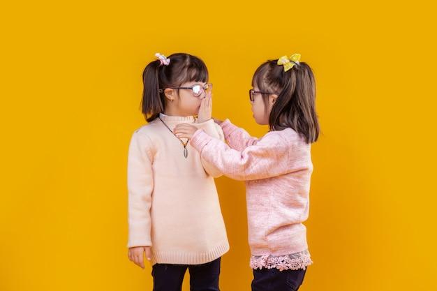 Mädchen mit unordnung. entzückende außergewöhnliche kinder mit down-syndrom, die miteinander sprechen und sich mit den händen berühren