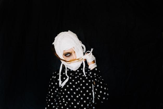 Mädchen mit verbundenem gesicht auf schwarzem hintergrund