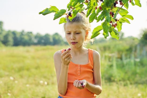 Mädchen mit vergnügen, das köstliche süße reife beeren vom maulbeerbaum isst