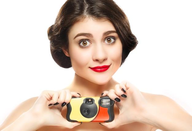 Mädchen mit vintage point-and-shoot-kamera lokalisiert auf weiß