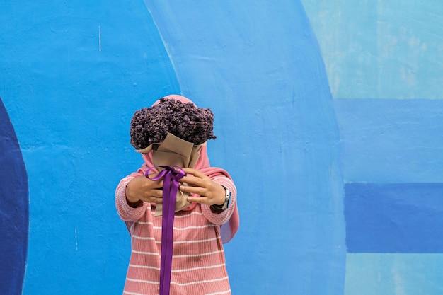 Mädchen mit violettem blumenstrauß an der blauen wand
