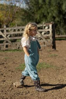 Mädchen mit vollem schuss, das auf der farm geht