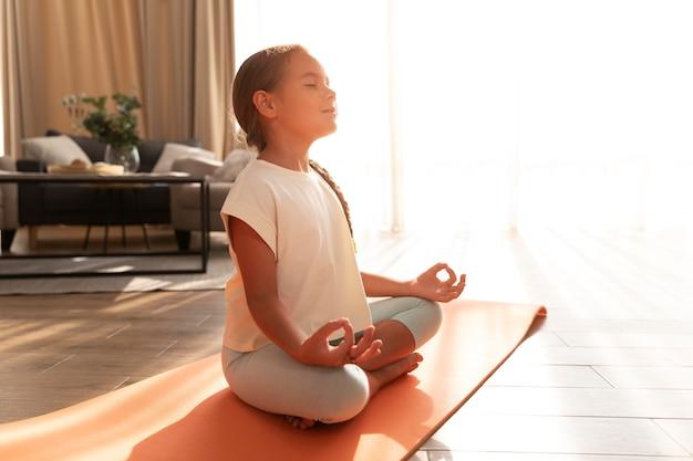Mädchen mit vollem schuss, das auf yogamatte meditiert