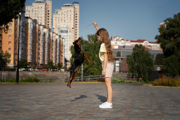 Mädchen mit vollem schuss, das mit hund spielt