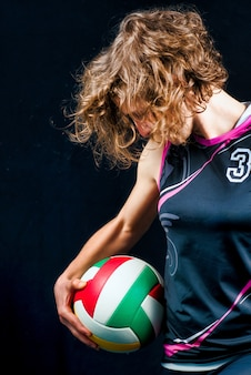 Mädchen mit volleyballball auf einem schwarzen hintergrund