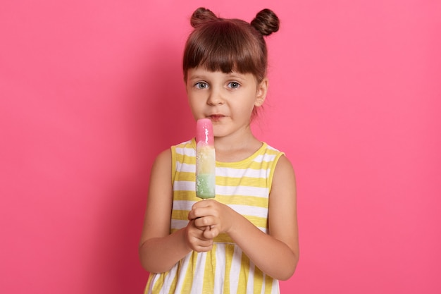 Mädchen mit wassereis, das direkt in die kamera schaut, isoliert über rosigem hintergrund aufwirft, kleidet gestreiftes weißes und gelbes outfit, das mit lustigen knoten steht, schaut in die kamera.