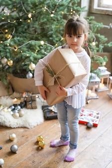 Mädchen mit weihnachtsbaum und geschenk