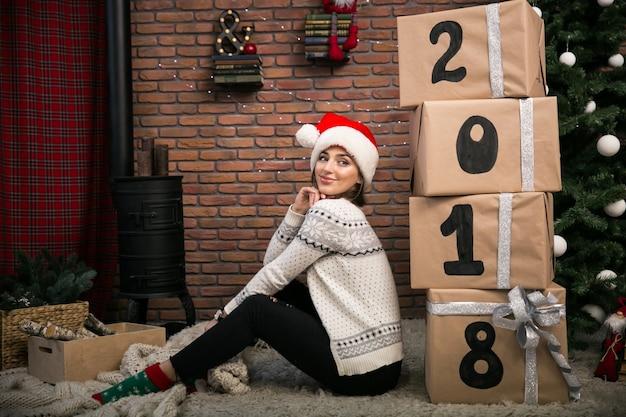 Mädchen mit weihnachtsgeschenken durch den weihnachtsbaum