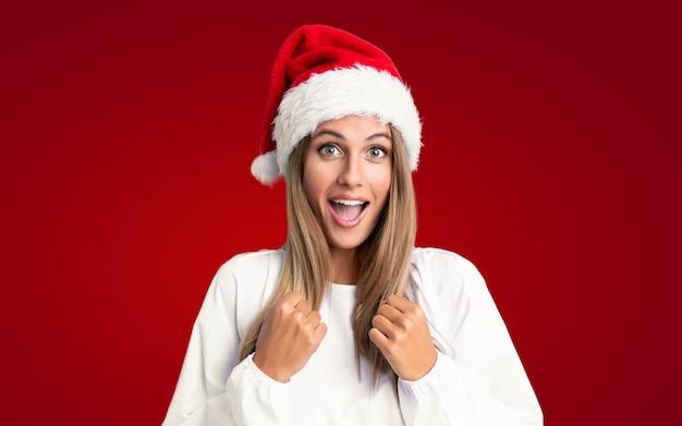 Mädchen mit weihnachtshut einen sieg feiernd