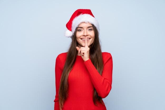 Mädchen mit weihnachtshut über dem lokalisierten blau, das ruhegeste tut