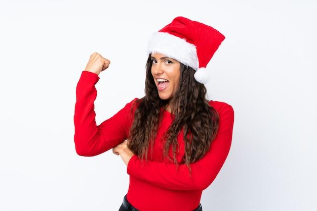 Mädchen mit weihnachtshut über dem lokalisierten weiß, das starke geste macht