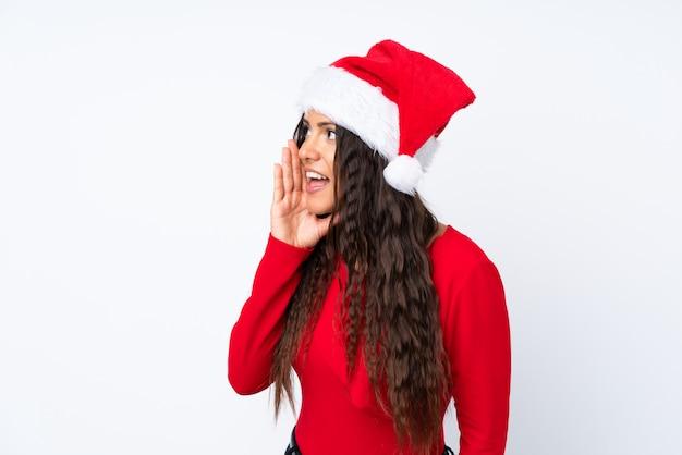 Mädchen mit weihnachtshut über dem lokalisierten weißen hintergrund, der mit dem breiten mund schreit, öffnen sich