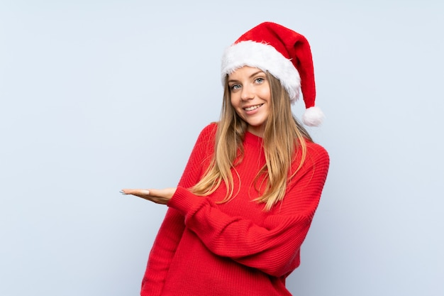 Mädchen mit weihnachtshut über den erweiterungshänden der lokalisierten blauen wand zur seite, damit die einladung kommt