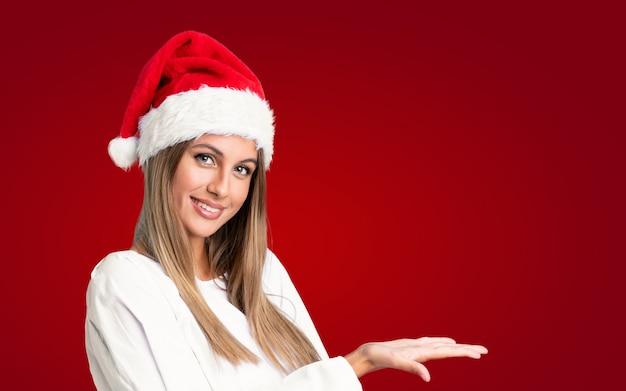 Mädchen mit weihnachtshut über den erweiterungshänden der lokalisierten wand zur seite, damit die einladung kommt