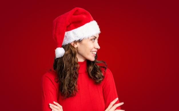 Mädchen mit weihnachtshut über der lokalisierten gelben wand, die zur seite schaut