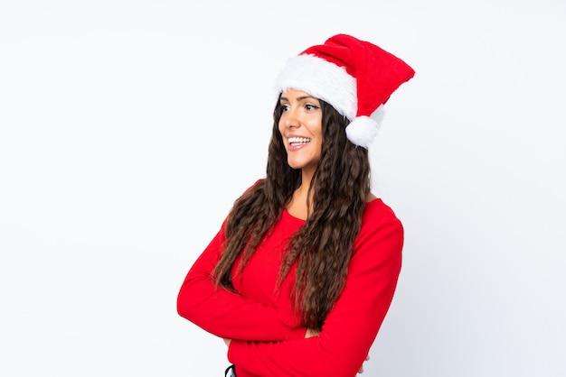 Mädchen mit weihnachtshut über getrenntem weißem schauen zur seite