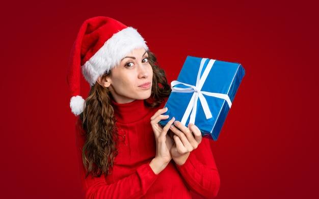 Mädchen mit weihnachtshut über getrennter roter wand