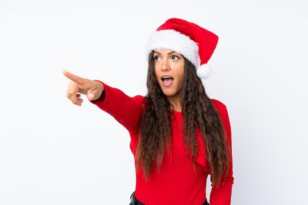 Mädchen mit weihnachtshut über lokalisiertem weißem hintergrund weg zeigend