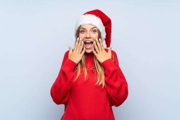 Mädchen mit weihnachtshut über lokalisierter blauer wand mit überraschungsgesichtsausdruck