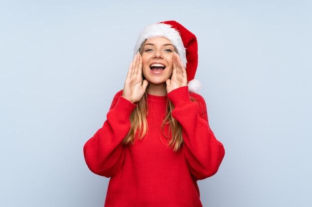Mädchen mit weihnachtshut und schreien über blauem hintergrund