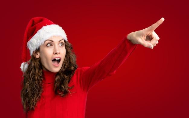 Mädchen mit weihnachtshut weg zeigend