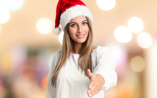 Mädchen mit weihnachtshuthändeschütteln nach viel