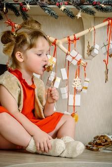 Mädchen mit weihnachtslebkuchen und geschenken, die an einem zweig hängen