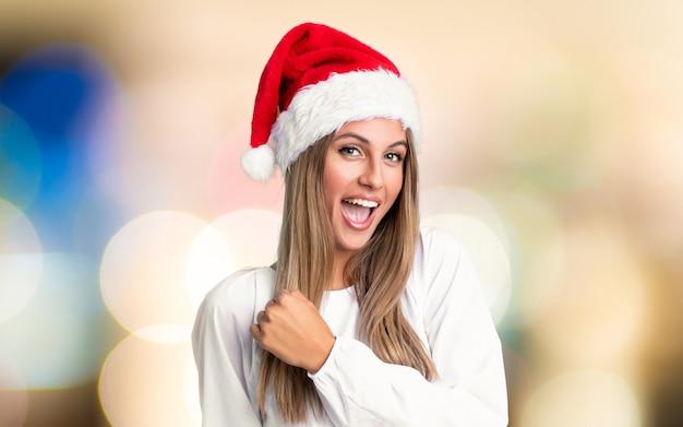 Mädchen mit weihnachtsmütze einen sieg über unfocused wand feiernd