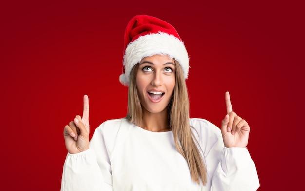 Mädchen mit weihnachtsmütze zeigt mit dem zeigefinger eine großartige idee