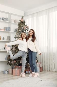 Mädchen mit weihnachtsspielzeug. frauen zu hause. schwestern bereiten sich auf die ferien vor.