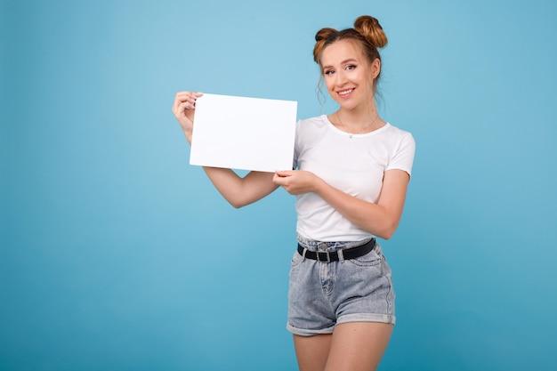 Mädchen mit weißem plakat auf einem blauen raum