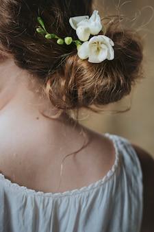 Mädchen mit weißen freesienblüten im haar