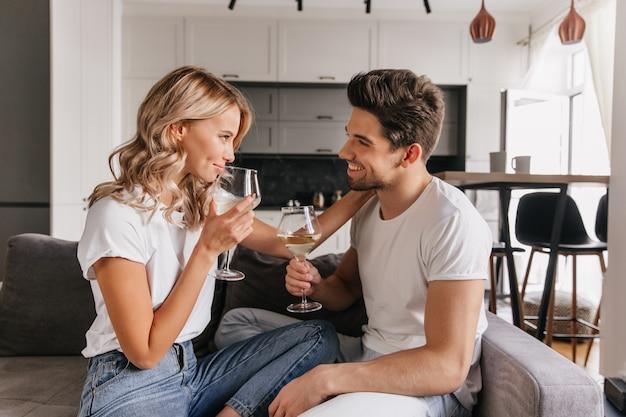 Mädchen mit welligem haar, das freund beim trinken des weins betrachtet. innenporträt des romantischen paares, das datum genießt.