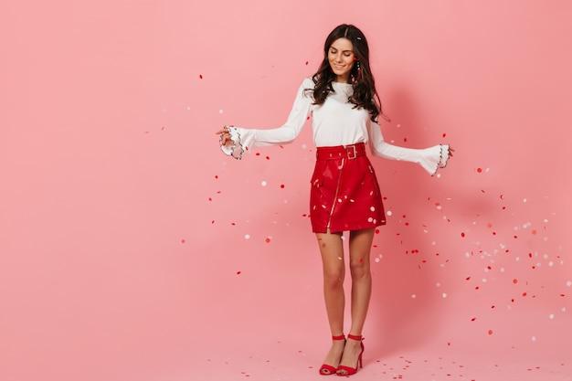 Mädchen mit welligem langem haar genießt konfetti, die auf rosa hintergrund fallen. dame im roten weißen outfit süß lächelnd.