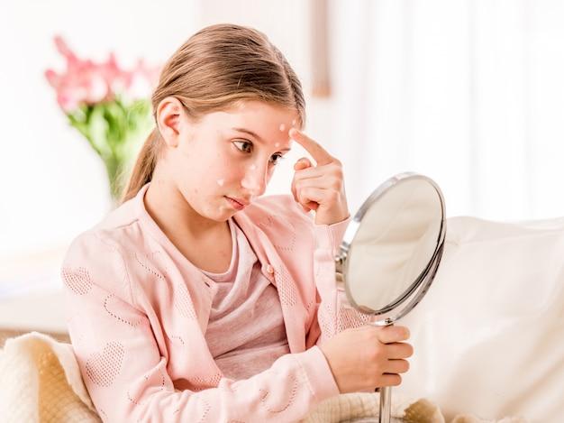 Mädchen mit windpocken, die den spiegel betrachten