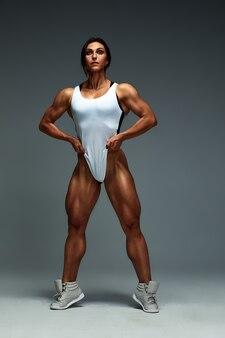 Mädchen mit wunderschönem muskulösem körper in einem weißen badeanzug auf grauem hintergrund. fitness. muskulöser körper.