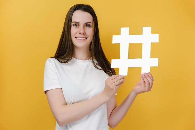 Mädchen mit zahnigem lächeln zeigen hashtag-symbol